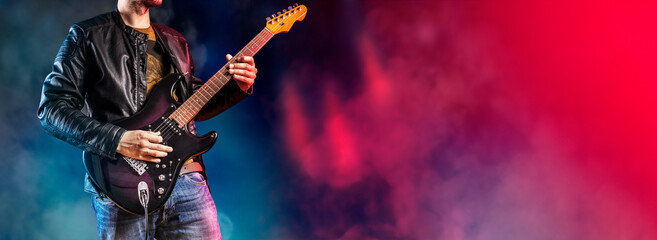 Guitar player performs on stage. Rock guitarist plays solo on an electric guitar. Artist and...
