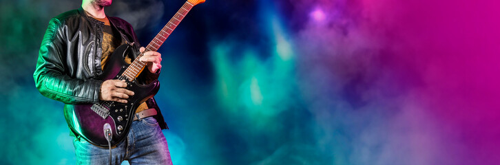 Guitar player performs on stage. Rock guitarist plays solo on an electric guitar. Artist and musician performs like rockstar. Black and white version. Green and pruple version. Panoramic image.