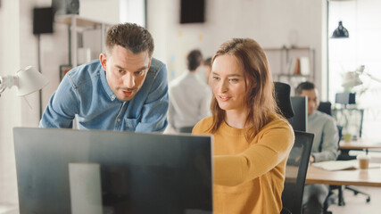 Female Specialist Works on Desktop Computer, Project Manager Stands Beside and gives Advice on Optimizing Workflow for Customer Experience Management. Modern Office with Diverse Team of Professionals