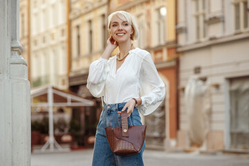 Street style photo of happy smiling fashionable woman wearing trendy white blouse, high waist...