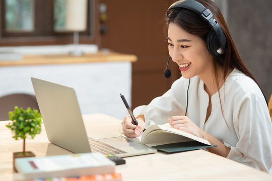 Smiling Asian young female using headset looking at laptop screen listen and learning online courses. Happy chinese business woman with headphones video call for customer service