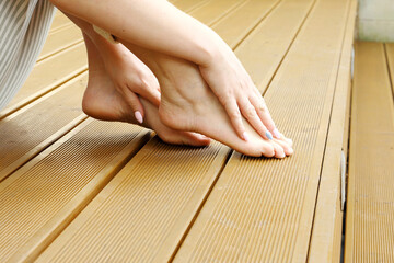 Beautiful bare female feet. A woman is standing barefoot on wooden floorboards.