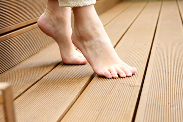 Feet care . A woman is standing barefoot on the wooden floor.