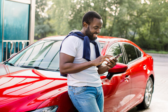 Cheerful casual hipster black man using smart phone and writing text messages, standing near his modern red car outdoors