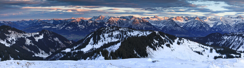 Wall Mural - Amazing sunset alpenglow panorama view to snow covered mountain ranges and dramatic sky in cold winter. View from Riedberger Horn to Allgau Alps Mountains. Bavaria, Germany.