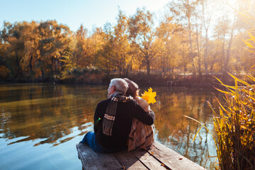 Senior family couple relaxing by autumn lake. Man and woman enjoying nature and hugging sitting on...