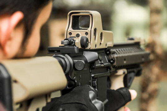 Military shooter with his precising assault rifle aiming and shooting target in the range