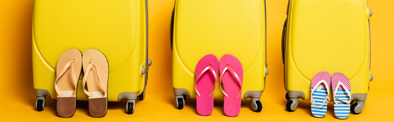 Poster Montagne travel bags with family flip flops isolated on yellow, panoramic shot