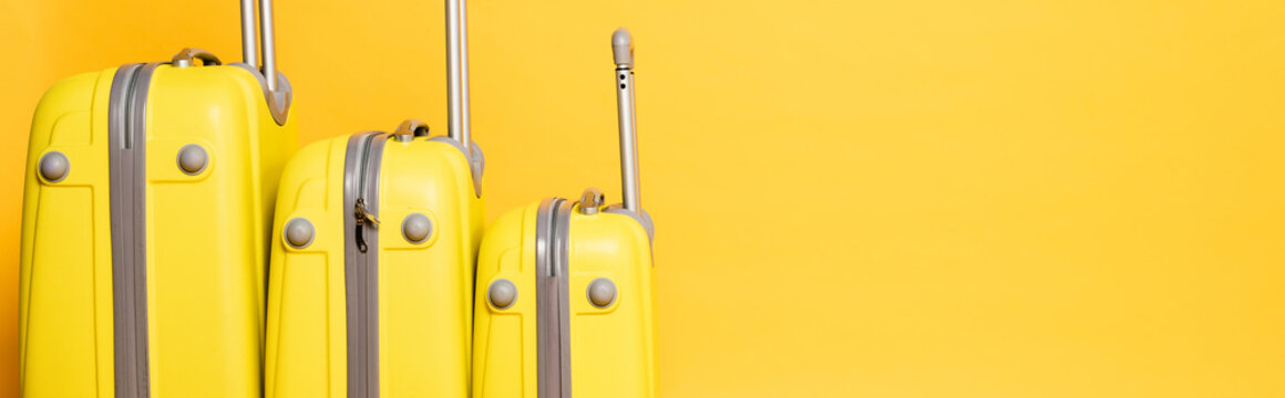 stack of travel bags isolated on yellow background, panoramic shot