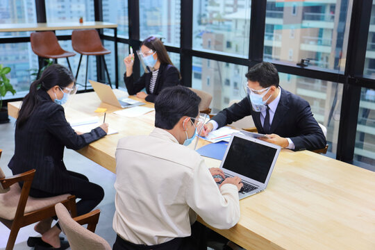 Asian people from various gender working together in co-working space following social distancing and new normal by wearing facial mask in the business office workplace during covid-19