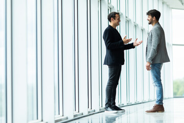Two businessmen deep in discussion together while standing in an office boardroom with windows overlooking the city