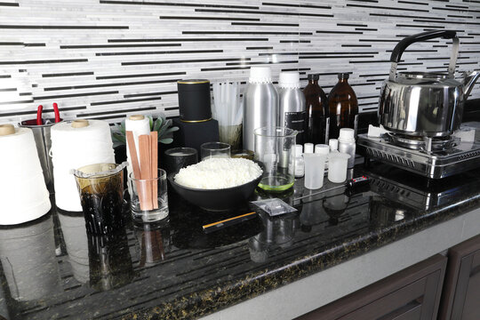 The material soy wax, fragrance and essential oil , wick and container tools for making candle are put on the marble table near the gas stove in the kitchen home