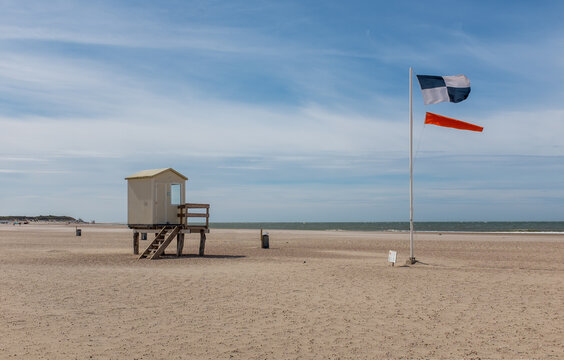 Lifeguard hut with windsock and safety flag on a beach in Zeeland, the Netherlands