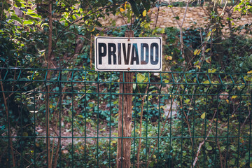 Poster on a fence in an orchard warning of private property.