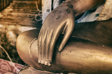 Closeup hand of Buddha Statue,old and rust from long life time,abstract art design background,blurry light around