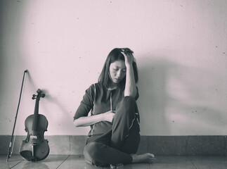 Lady sitting on ground floor,against on the wall,beside violin and bow,stress and tried feeling,vintage and art style,classic old film tone