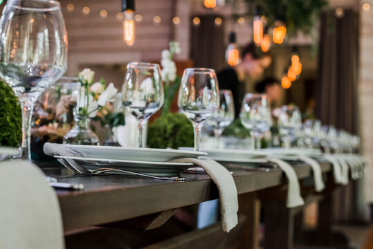 Wedding reception table with Edison bulbs and decor of greenery. Decoe. Wedding table setting