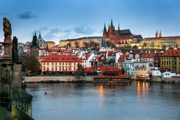 Illuminated Lesser town view from Charles Bridge in the evening, with Prague castle and Saint Nicholas church in Prague, Czechia