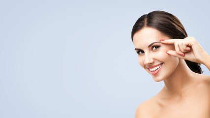 Portrait image of happy amazed, smiling beautiful woman pointing brow or eye, touching skin,...