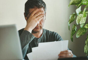 Sad man working with papers at home.
