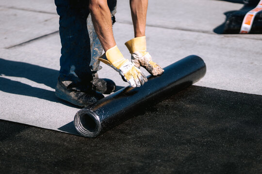 Professional workers waterproofing house construction site. Worker rolling membrane