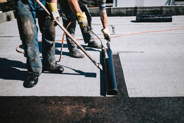 Construction workers insulating rooftop with bituminous membrane. Waterproofing details at construction site. Bituminous membrane waterproofing system details and installation on flat rooftop.