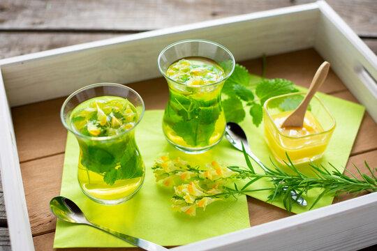 zwei Gläser mit frisch aufgebrühten Tee aus Zitronenmelisse und Leinkraut auf einem Tablett.