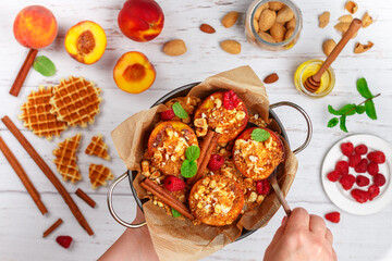 Baked peaches with ricotta, almonds, biscuit crumbs or Viennese (Belgian) waffles and cinnamon, served with honey, raspberries and mint. Delicious gourmet dessert.
