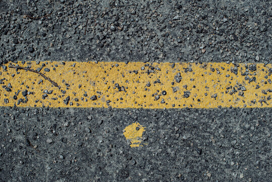Texture of asphalt and yellow road markings, line and dot, close up