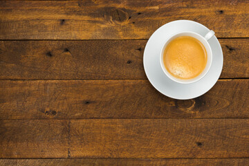 High angle view of coffee in white cup with saucer on old wooden background, close up