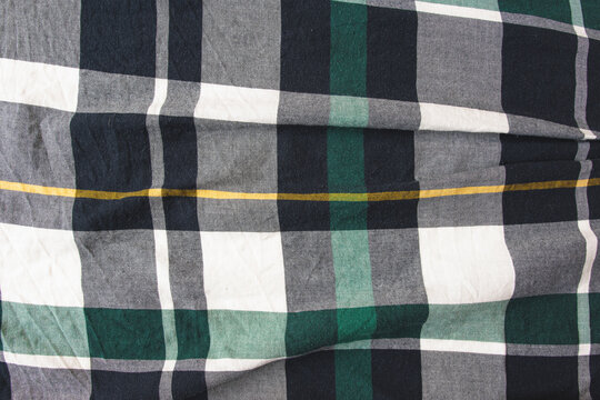 Flannel shirt seamless tartan pattern of green, grey, black and yellow fashion clothing. Checked lumber jack shirt material, close up top view of fashionable cloth design, empty cotton fabric