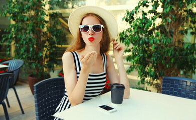 Attractive young woman blowing red lips sending sweet air kiss while sitting at a table in a cafe