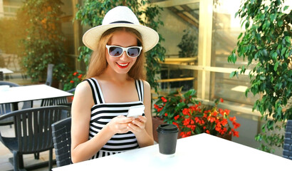 Beautiful young woman sitting at a table in a cafe with phone