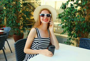 Beautiful young woman calling on smartphone sitting at a table in a cafe with coffee cup