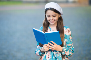 Girl student reading book outdoors, school of good manners concept