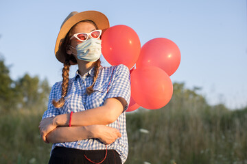 young woman with face mask and balloons posing