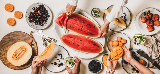 Summer tropical fruit party table. Flat-lay of lunch with fruit, berries, watermelon, lemonade and peoples hands over white background, top view. Vegan, clean eating, fruiterian food concept