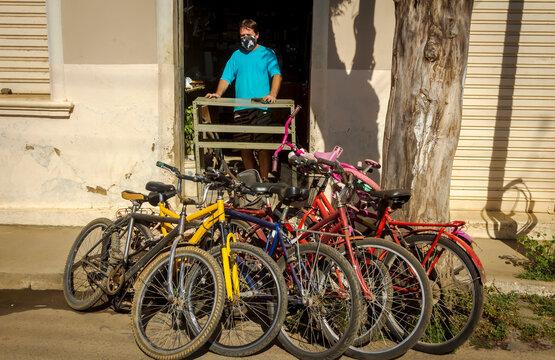 Mecânico de bicicleta usa máscara de proteção contra coronavírus no trabalho, em Guarani, Minas Gerais, Brasil