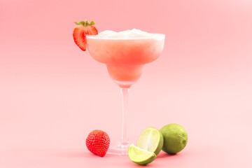 Mixed cocktails, party punch smoothies and frozen summer drinks concept with strawberry mojito or daiquiri in margarita glasses, strawberries and limes isolated on pink background