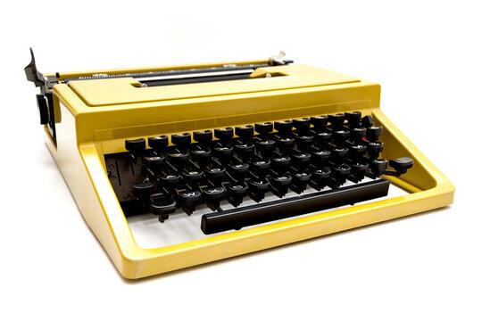 Vintage mustard yellow typewriter on a white background