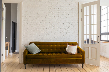 Soft couch with cushions located near rough wall and elegant doors in cozy living room at home