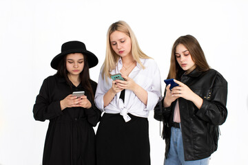 Three young beautiful girls are looking at their smartphones.