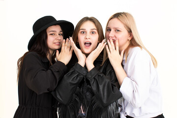 Three young beautiful girls are discussing the news and one is very surprised