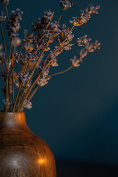Dried lavender in wooden vase on dark blue background with copy space.