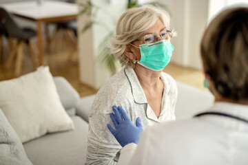 Mature woman with protective face mask communicating with her doctor at home.