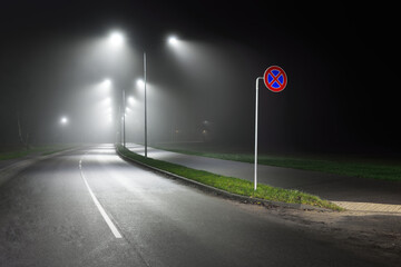 Illuminated empty highway in a fog at night. Street lights and road signs close-up. Dark urban scene, cityscape. Riga, Latvia. Dangerous driving, speed, freedom, concept image