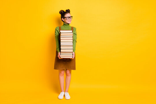 Full length body size view of her she attractive diligent cheerful girl nerd carrying many book back to school 1 September autumn fall isolated bright vivid shine vibrant yellow color background
