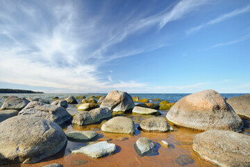 Rocky shore of the Baltic sea under a clear blue sky with cirrus clouds. Ancient stones close-up. Spring. Kasmu nature reserve, Estonia. Ecology, environmental conservation, eco tourism concepts
