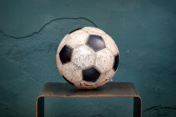 Old stained football on a small shelf