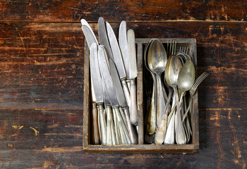 Collection of old vintage cutlery in a wooden tray